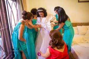 helping the brides with the dress